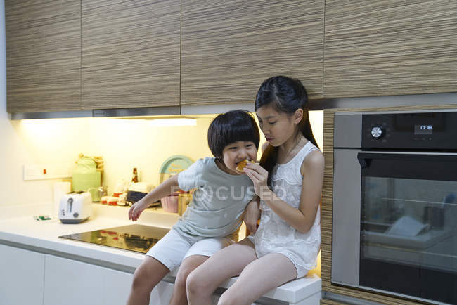 Happy young asian family together eating at kitchen — Stock Photo