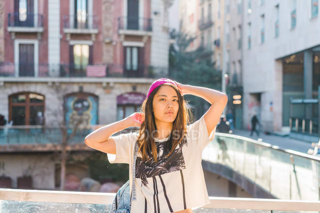Young attractive asian woman posing on city street — Stock Photo