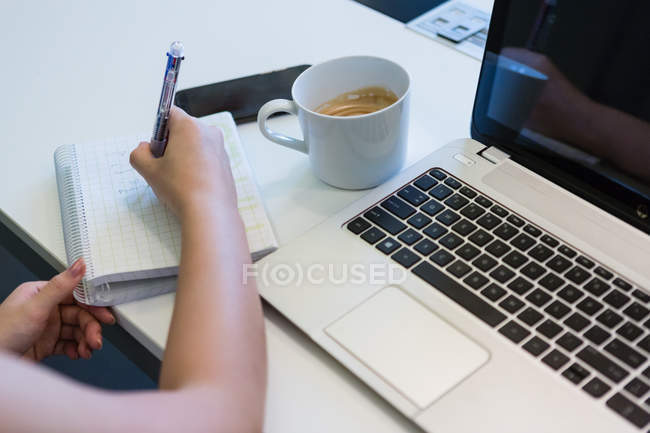 Cropped image of woman working with laptop and notebook in modern office — Stock Photo