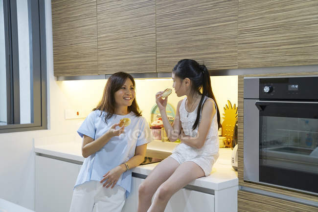 Young asian mother and daughter together eating at kitchen — Stockfoto