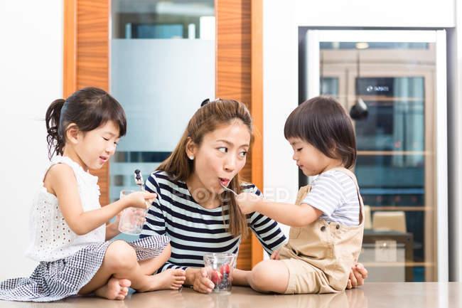 Женщина, наслаждаясь здоровые закуски время со своими детьми — стоковое фото