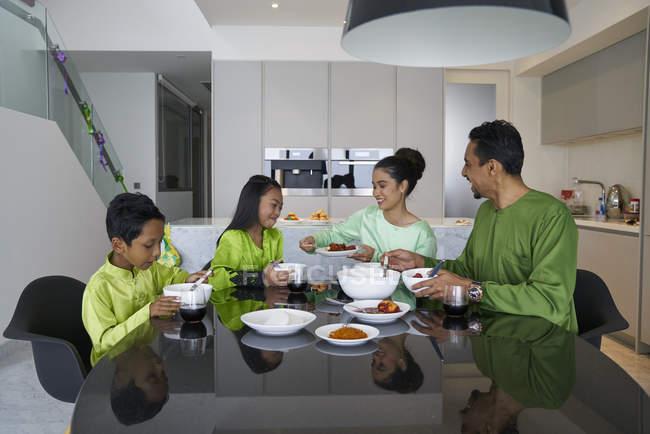 Familia asiática joven celebrar Hari Raya juntos en casa - foto de stock