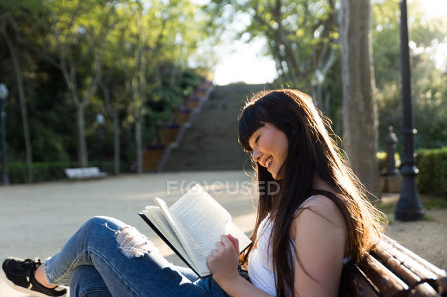 Young Eurasian woman reading a book on bench — Stock Photo