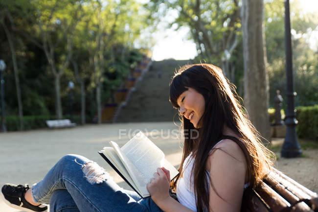 Junge eurasische Frau liest ein Buch auf Bank — Stockfoto