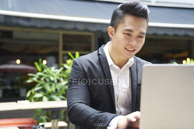 Young asian successful business  man using laptop — Stock Photo