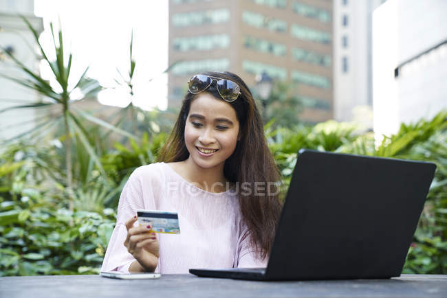 Beautiful Malay lady making an online purchase with her credit card — Stock Photo