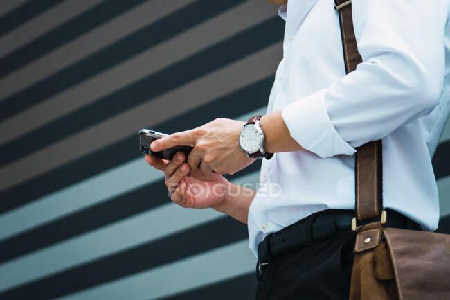 Junge asiatische Geschäftsmann in der Stadt mit Handy — Stockfoto