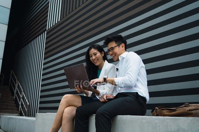 Young asian business couple working with laptop — Stock Photo