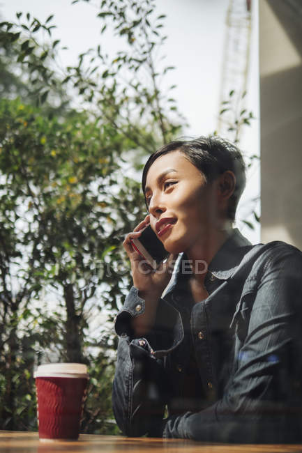 Young attractive asian woman using smartphone and having coffee — Stock Photo