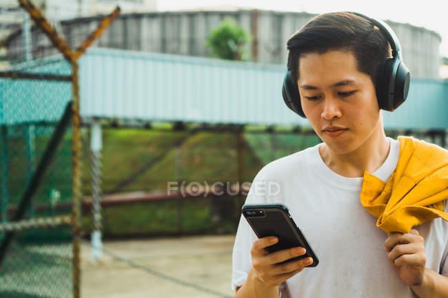 Jovem homem elegante asiático usando smartphone — Fotografia de Stock