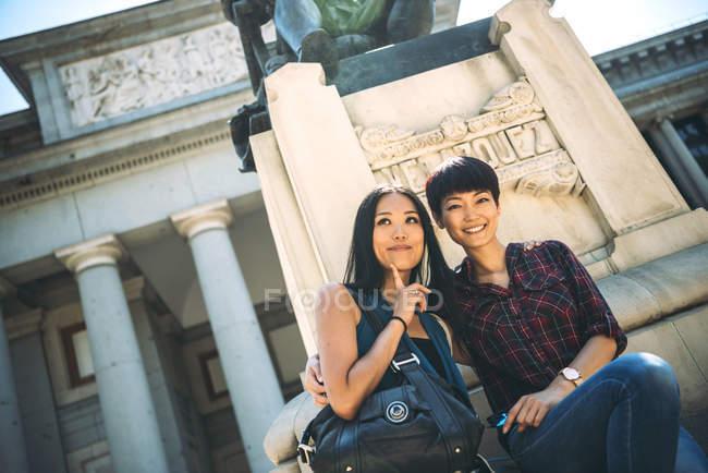 Turistas mujer asiáticos sentada fuera de un museo - foto de stock