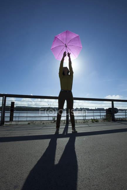 Image verticale éclairée en noir de la femme tenant un parapluie rose sur un ciel bleu matin avec une ombre incroyable sur le sol . — Photo de stock