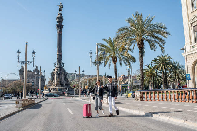 Young tourist couple crossing the road at the Columbus monument with a suitcase, spain — Stock Photo