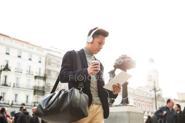 Hombre chino joven casual con un equipo tablet PC. auriculares y una taza de café en la Puerta del Sol, Madrid, España - foto de stock