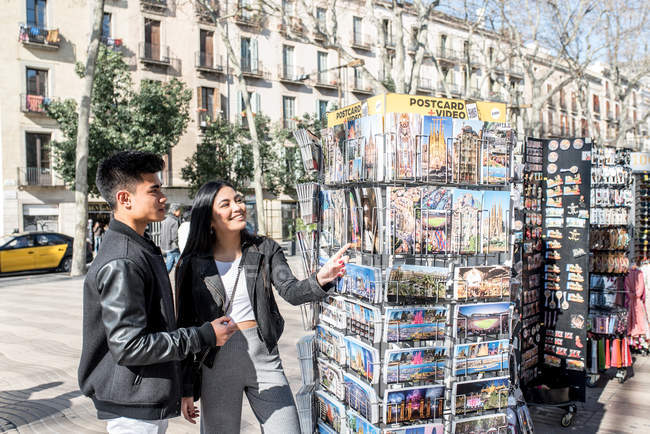 Young asian couple shopping in las ramblas in Barcelona, spain — Stock Photo