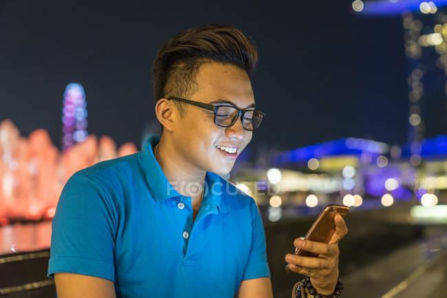 Joven jugando con su Smartphone en la ciudad - foto de stock