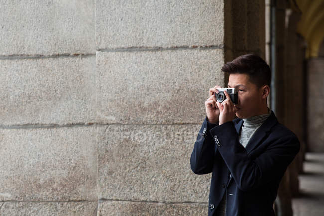 Casual young chinese man taking pictures with a vintage photo camera in Madrid, Spain — Stock Photo