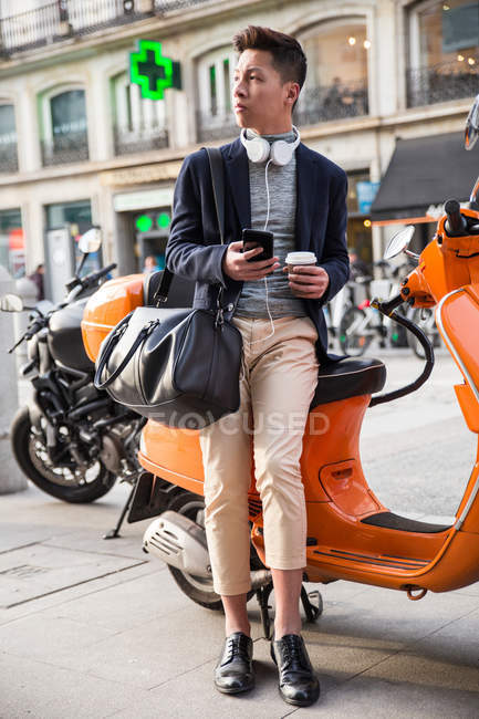 Casual young chinese man with a smart phone. sitting on a motorbike at Puerta del Sol, Madrid, Spain — Stock Photo