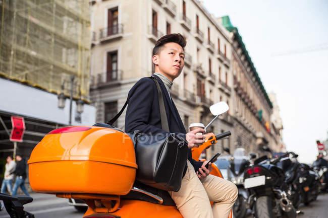 Hombre chino joven casual con un teléfono inteligente sentado en una moto en la Puerta del Sol, Madrid, España - foto de stock