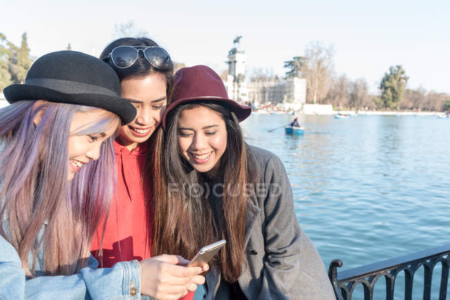 Mujeres mirando su smartphone en Retiro Parque de Madrid, España - foto de stock