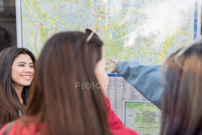 Tres mujeres en España mirando la pizarra Mapa - foto de stock