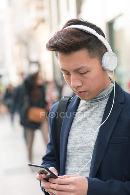 Casual young chinese man using phone and headphones in the street, Spain — Stock Photo