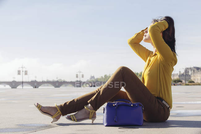 Chinese woman sitting and enjoying the sun — Stock Photo