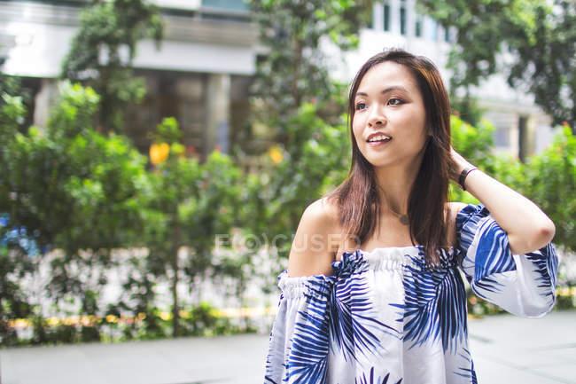 Schön asiatische Mädchen zu Fuß die Straße hinunter. — Stockfoto