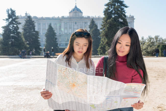 Asian women doing tourism in Madrid with a map, Spain — Stock Photo