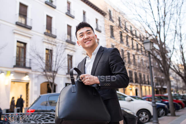 Portrait of a cheerful chinese businessman in the street - foto de stock