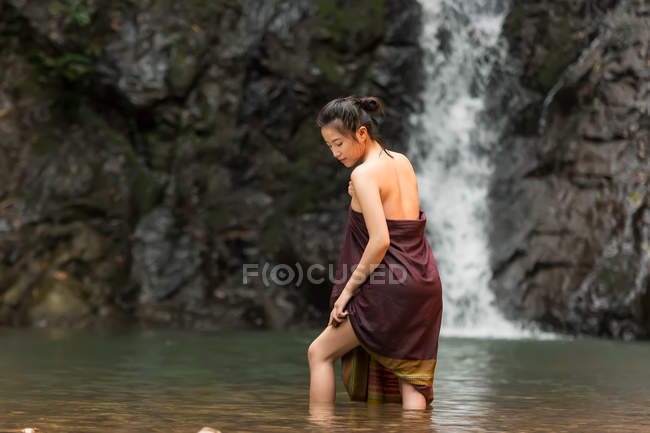 Attractive asian young woman relaxing near waterfall in Thailand — Stock Photo