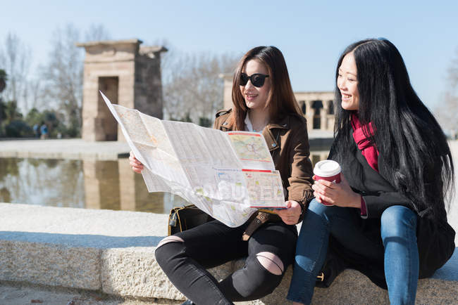 Asian women doing tourism in Madrid and looking at a city map, Spain — Stock Photo