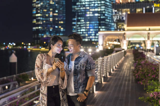 Junges Paar mit dem Smartphone In Großstadt spielen — Stockfoto