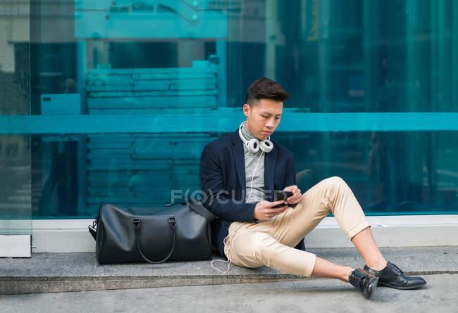 Случайный молодой китаец, сидящий на улице по телефону — стоковое фото