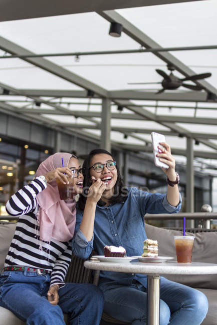 Two Women Enjoying Their Time At A Cafe And Taking Selfie — Stock Photo