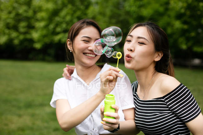 Милые азиатские подружки делают мыльные пузыри в парке . — стоковое фото