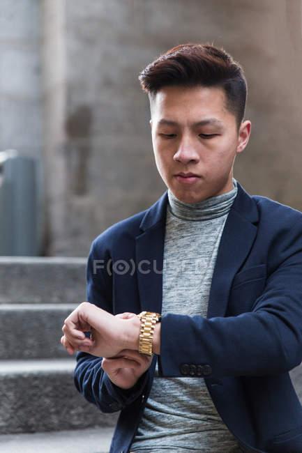 Petit chinois décontracté vérifiant l'heure en regardant sa montre dans la rue, Espagne — Photo de stock