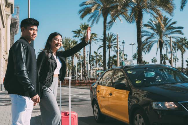 Giovane coppia turistica che sventola un taxi per strada a Barcellona, Spagna — Foto stock