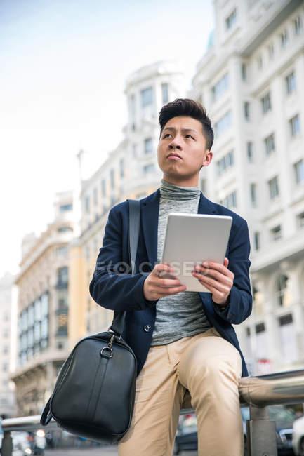 Випадковий китайський зображений юнаком iз планшетного комп'ютера на вулиці Гран Віа, Мадрид, Іспанія — стокове фото