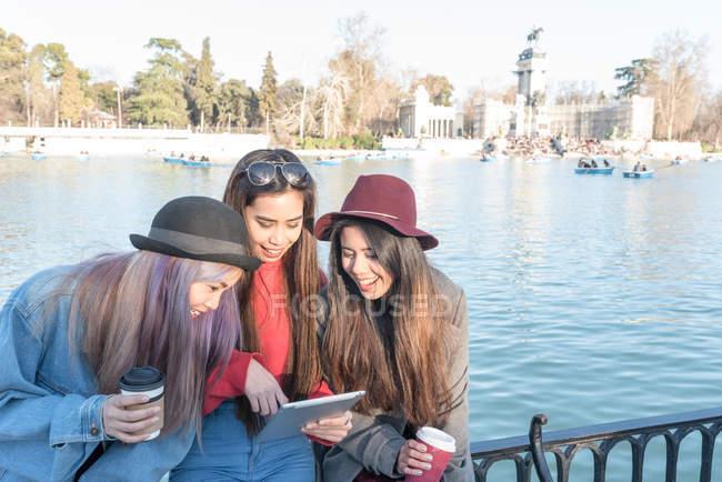 Jovens mulheres de cabelos longos navegando e olhando para seu tablet, Espanha — Fotografia de Stock