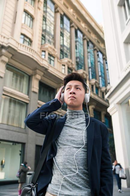 Jovem chinês casual ouvindo música na rua Gran Via, Madri, Espanha — Fotografia de Stock