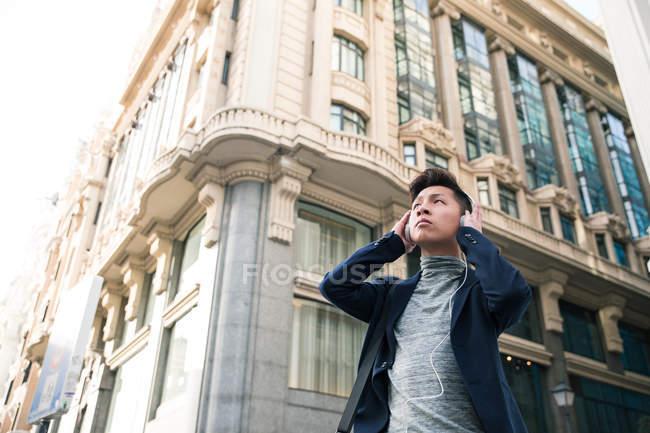 Випадковий китайський юнак прослуховування музики на вулиці Гран Віа, Мадрид, Іспанія — стокове фото