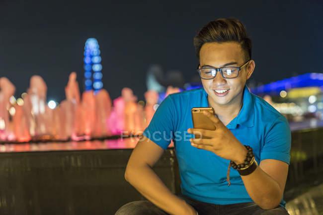 Молодой человек играет со своим смартфоном в городе — стоковое фото