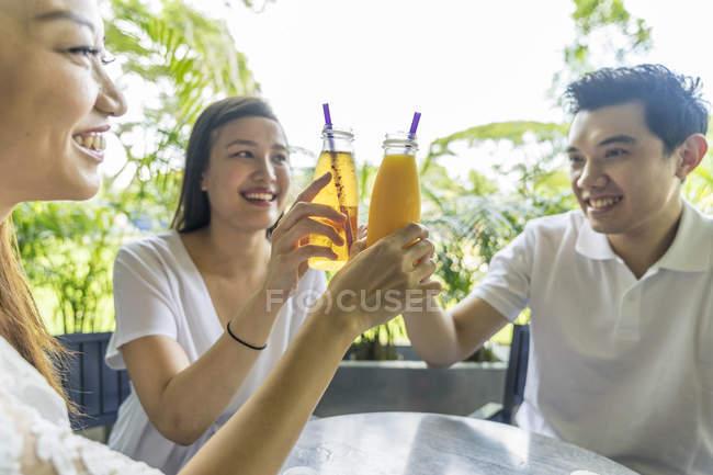 Amigos haciendo los aplausos juntos en el café - foto de stock