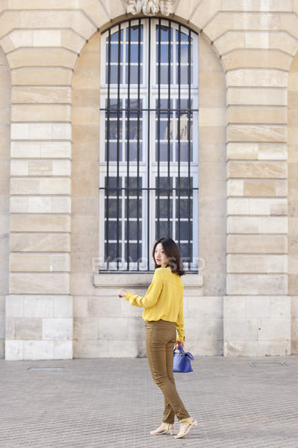 Young woman with handbag posing against building — Stock Photo