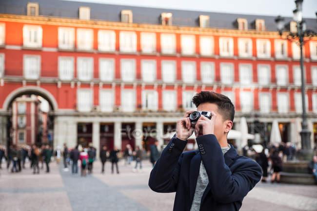 Casual hombre chino joven tomando fotos en la Plaza Mayor, Madrid, España - foto de stock