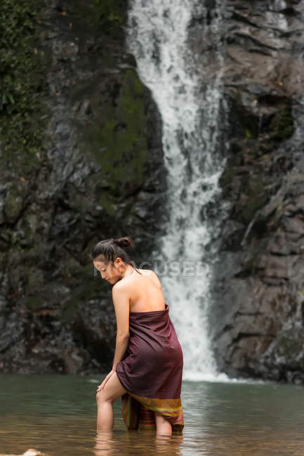 Attractive asian young woman relaxing near waterfall in Thailand - foto de stock