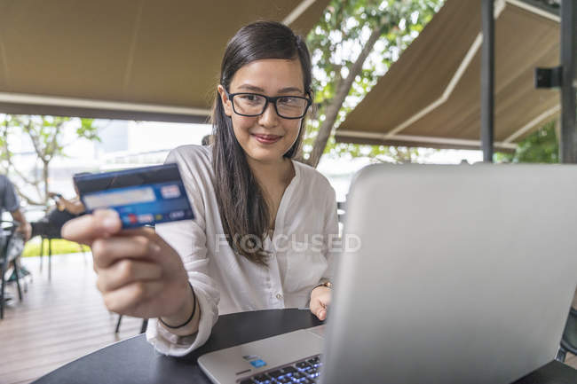 Young beautiful asian woman making transaction with laptop — Stock Photo