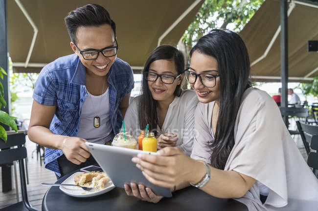 A Group Of Friends Sharing Something Interesting On Their Gadgets. — Stock Photo