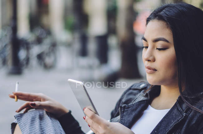 Portrait of a young asian woman smoking a cigarette and on the mobile phone in Barcelona, spain — Stock Photo